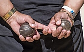 Two metal balls for game in pétanque in man´s hands.