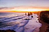 Dramatic sunset view of the famous Twelve Apostles limestone stacks off the shore of Port Campbell National Park on the Great Ocean Road, Victoria, Australia.