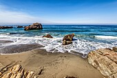 Rock formations in the ocean off of a beach. Big Sur, California, United States.