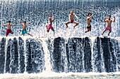 Boys jumping in a waterfall and having fun, Bali, Indonesia.