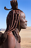 Namibia Africa remote nomadic Himba tribe young woman portrait in desert with traditional dress in desert of Hartmann Berge in Namib Desert t black girl.