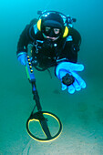 Diver with the metal detector displays the found ancient coins, lake Baikal, Siberia, Russia, Eurasia.
