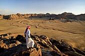 Bedouin and view from the mountain Jebel Khasch. Jordan, Wadi Rum desert, border with Saudi Arabia. Model Released.