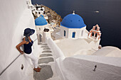 Woman in front of a blue domed church in Oia town with a ferry at the background, Santorini, Cyclades Islands, Greek Islands, Greece, Europe.