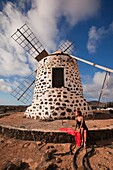 Woman posing in front of the windmill near Tefia, La Oliva, Fuerteventura, Canary Islands, Spain, Europe.