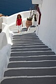 Woman walking up the stairs in town center, Oia, Santorini, Cyclades Islands, Greek Islands, Greece, Europe.