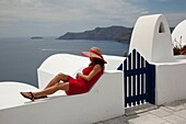 Woman in red dress sitting near a hotel entrance looking down to Caldera in Oia town, Santorini, Cyclades Islands, Greek Islands, Greece, Europe.
