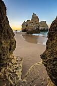 Photographer in action close to the cliffs and ocean at dawn Praia da Rocha Portimao Faro district Algarve Portugal Europe.