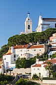 View of a residential district of Lisbon surrounded by trees and church under a blue summer sky Portugal Europe.