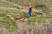 Athletic woman running on a trail through the fields of Boulder, Colorado