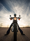 Centered perspective of a woman sitting on her vintage motorcycle wearing a reflective helmut face shield with the sun setting in the background