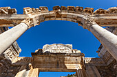 'Low angle view of an arch in ancient ruins against a blue sky; Ephesus, Turkey'