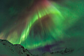 The aurora borealis towers over the Talkeetna Mountains in Hatcher Pass State Recreation Area, Alaska.