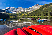 'Mountain lake with dock reflecting snow peaks and blue sky with upside down red canoes in the foreground; Waterton, Alberta, Canada'