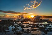 'Waves crash over a rock outcrop at sunrise; Kauai, Hawaii, United States of America'