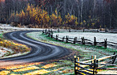 'Wooden rail fence in a frost covered grass field with trees in autumn colours and a winding road; Iron Hill, Quebec, Canada'