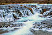 'Water cascading over rocks and flowing into a river; Bruarfoss, Iceland'