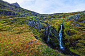 'A small waterfall tumbles down the mountain side in one of Iceland eastern fjords; Iceland'