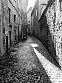 'Narrow cobblestone alley between buildings; Orvieto, Umbria, Italy'