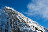 'Close up of a snow covered mountain peak with wind blowing snow off the slope with blue sky and clouds; Kananaskis Country, Alberta, Canada'