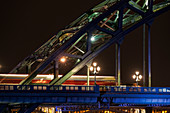 Close up of the illuminated arch of a bridge and lamp posts at nighttime