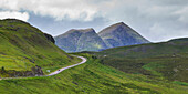 'A road winding through the mountains with two mountain peaks under a cloudy sky in the Highlands; Scotland'