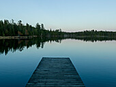 'Wooden dock leading out to a tranquil lake at sunrise; Whiteshell, Manitoba, Canada'