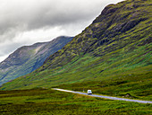 'A vehicle travels on a road beside rugged mountains under a cloudy sky; Scotland'