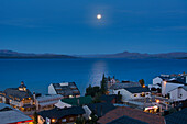 'The moon rising over a lake from above the town roof tops showing some yellow city lights against the blue scene; Bariloche, Argentina'