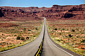 'Utah highway stretching into the distance with rock cliffs and blue skies in the background and desert vegetation on either side of the road; Utah, United States of America'