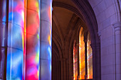 'Light streaming through stained glass windows with colourful light columns along the cathedral nave; Washington, District of Columbia, United States of America'