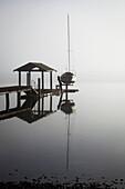 'Sailboat on lift by dock on foggy lake; Bellingham, Washington, United States of America'