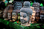 'Heads of statues of Buddha are stacked in a terra-cotta factory; Chiang Mai, Thailand'