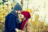 'A young couple looking into each other's eyes and kissing in a city park in autumn; Edmonton, Alberta, Canada'