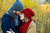 'A young couple holding each other closely and looking into each other's eyes in a city park in autumn; Edmonton, Alberta, Canada'