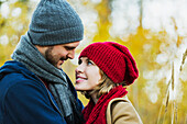 'A young couple looking into each other's eyes in a city park in autumn; Edmonton, Alberta, Canada'