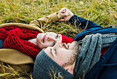 'A young couple laying in the grass and holding hands in a city park in autumn; Edmonton, Alberta, Canada'