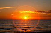 'A halo around the glowing sun as it sets over the ocean and an orange sky; Chiclana de la Frontera, Andalusia, Spain'