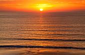 'A golden sun sinking into the horizon over the ocean; Andalusia, Spain'