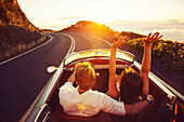 Happy Couple Driving on Country Road into the Sunset in Classic Vintage Sports Car