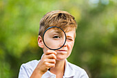 'A young boy using a magnifying glass in a park; Edmonton, Alberta'