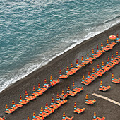 'Rows of colourful lounge chairs and umbrellas on a beach at the water's edge; Positano, Campania, Italy'