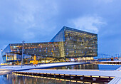 'Exterior view of the Harpa Public Concert Hall, designed by the Danish firm Henning Larsen Architects and Icelandic firm Batteriao Architects, the glass facade was designed by Icelandic glass artist Olafur Eliasson at twilight; Reykjavik, Iceland'