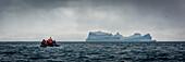 'Inflatable motors towards blue iceberg on horizon; Antarctica'