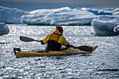 'Backlit kayaker paddling by icebergs in sunlight; Antarctica'