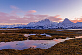 Scenic view of the Chugach Mountains at sunset reflecting in the tidal flats near Valdez, South-central Alaska, winter
