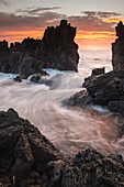 'Surf comes in through rocks at sunrise; Laupahoehoe, Island of Hawaii, Hawaii, United States of America'