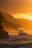 'Surf breaks on the Na Pali coast at sunset; Kauai, Hawaii, United States of America'