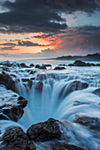 'Surf spills into a hole in a rock shelf along the coast in northeastern Kauai; Kauai, Hawaii, United States of America'