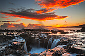 'Surf spills into a hole in a rock outcrop at sunrise on the east side of Kauai; Kauai, Hawaii, United States of America'